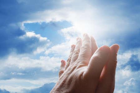 Foto de Hands praying in the sky - Imagen libre de derechos