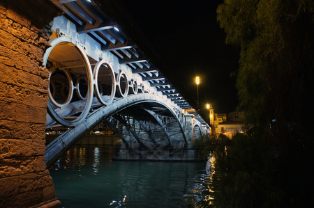 Night view of the Triana Bridge (Puente de Isabela II) on the Canal de Alfonso XIII of Guadalquivir in Seville, Spain