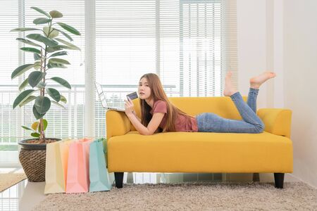 Photo pour young asian woman sitting on the yellow sofa using laptop and cradit card shopping online near window and shopping bag - image libre de droit