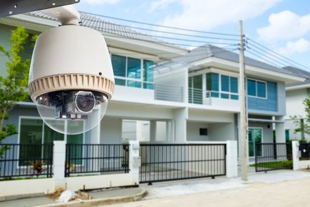 Photo pour CCTV Camera or surveillance operating with house village in background - image libre de droit