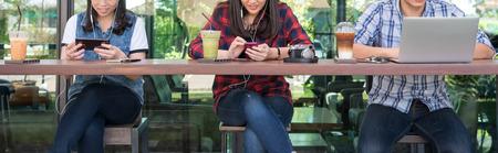 Foto de three people using smartphone, tablet, and laptop in coffee shop, internet of things conceptual - Imagen libre de derechos