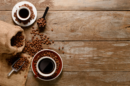 Foto de Top view of a cup of americano with coffee bean bag, sugar and cinnamon on wood background floor - Imagen libre de derechos