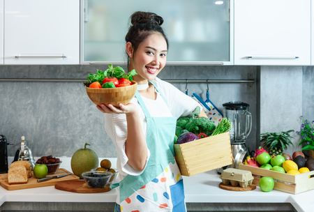 Woman in kitchen with various kind of vegetable and fruits that all are good for health and no meat, vegan lifestyle