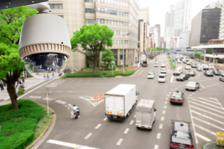 Foto de CCTV Surveillance camera operating on traffic road and people cross road in japan - Imagen libre de derechos