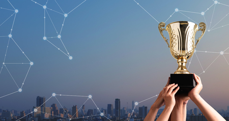 Photo pour Winning team raise trophy cup with digital background, digital achievement conceptual - image libre de droit