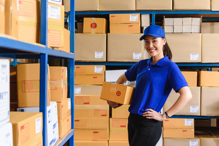 Photo pour Portrait of woman delivery staff in blue uniform holding parcel box size D in warehouse - image libre de droit