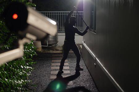 Photo pour Thief use crowbar break into a house at window being caught by CCTV, surveillance camera - image libre de droit