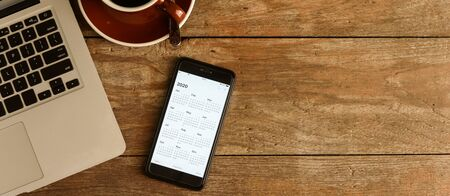 Photo pour Screen of smartphone with calendar of year 2020 with laptop and organizer on coffee table - image libre de droit