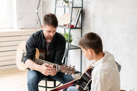 The young teacher shows the correct position of the hands in the guitar on his example