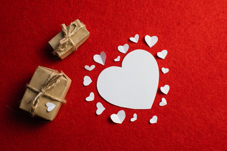 Photo pour Cutouts of white paper in the form of a hearts and brown gifts with bows for Valentine's day. Holiday of love - image libre de droit
