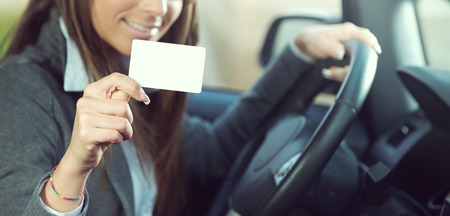 Young smiling woman driving a car and holding a business identification card or driver's license.