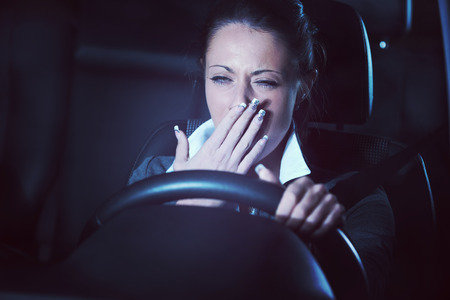 Distracted exhausted tired woman driving a car late at night.