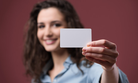 Young smiling woman holding a blank business card