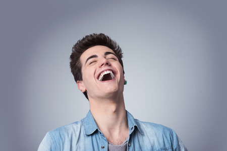 Funny smiling guy laughing out loud with closed eyes