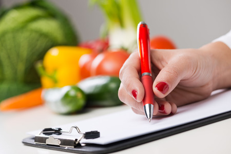 Nutritionist writing medical records and prescriptions with fresh vegetables
