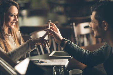 Foto de Young fashionable couple at the bar using a mobile touch screen phone - Imagen libre de derechos