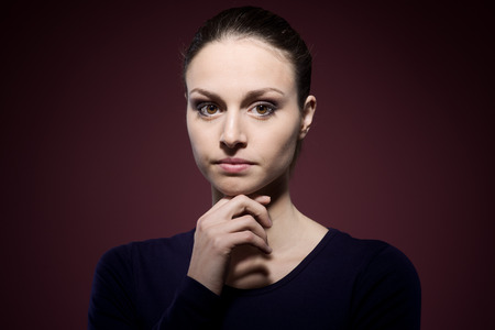 Pensive young woman posing with hand on chin