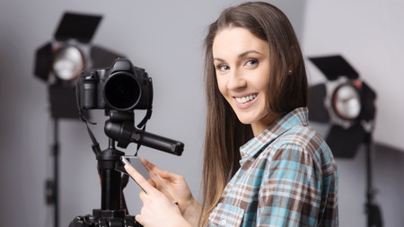 Young female photographer posing with a digital camera on tripod and lighting equipment on background
