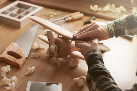 Photo pour Craftsman smoothing a wooden toy surface with sandpaper, tools and wood shavings all around, hands close up - image libre de droit