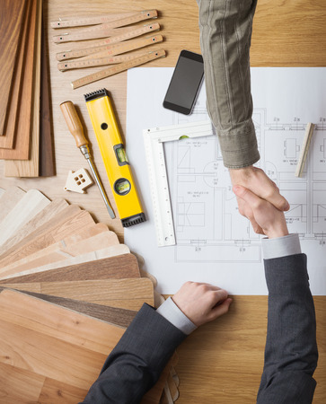 Photo pour Customer businessman and construction engineer working together on a building project, they are shaking hands, desktop with draft and tools  - image libre de droit