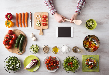 Man's hand cooking at home with touch screen tablet, fresh vegetables and kitchen utensils all around, top view
