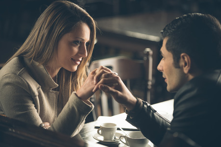 Romantic couple dating at the bar with hands clasped