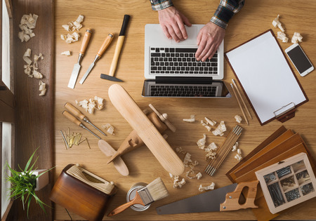 Photo pour Man working on a DIY project with his laptop, wood shavings and carpentry tools all around, top view - image libre de droit
