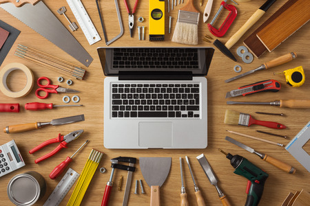 Laptop on a work table with DIY and construction tools all around, top view, hobby and crafts concept