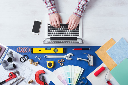 Photo pour Male hands using a laptop next to plumbing work tools, tiles and swatches, online booking and home plumber service - image libre de droit