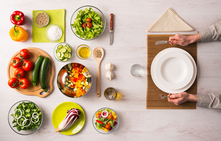 Healthy vegetarian meal concept with table set, hands holding fork and knife and fresh raw vegetables