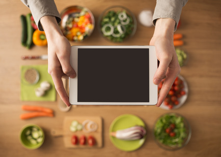 Hands holding a digital touch screen tablet with fresh vegetables and kitchen utensils