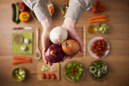 Hands holding different types of onions with fresh raw vegetables and salad bowls