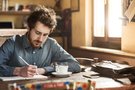 Young  man sketching on a notebook in his studio on a rustic wooden table