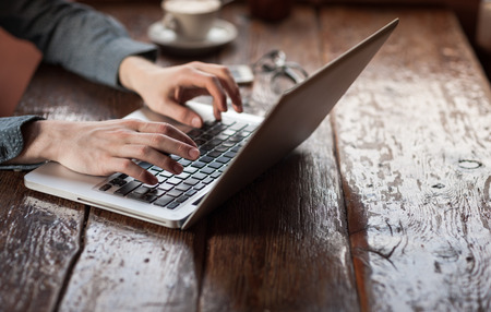 Man working on a laptop on a rustic wooden table, hands close upの写真素材