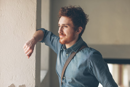 Young man looking away and leaning on a wall