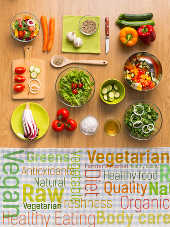 Healthy fresh vegetarian food on kitchen table with healthy eating text concepts on a checked tablecloth, top view