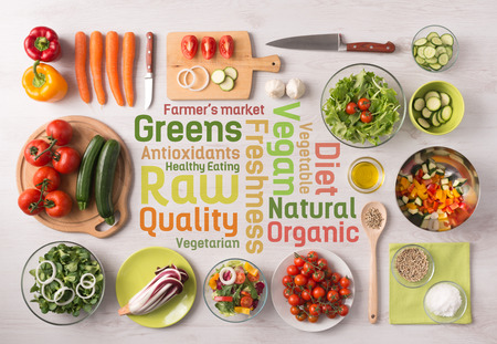 Healthy fresh vegetables salad preparation with kitchen utensils on a table and nutrition text concepts