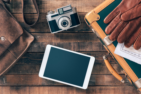 Photo pour Vintage hipster traveler packing ready to leave with camera and digital touch screen tablet, top view - image libre de droit