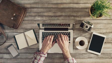 Photo pour Hipster vintage wooden desktop top view, male hands typing on a laptop - image libre de droit