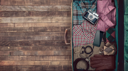 Hipster traveler vintage ready suitcase with camera and clothing, blank copy space, top view