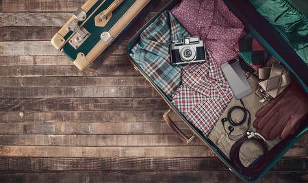 Foto de Hipster traveler vintage ready suitcase with camera and clothing, blank copy space, top view - Imagen libre de derechos
