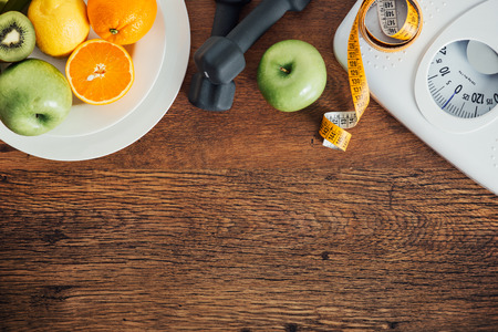 Foto de Fitness and weight loss concept, dumbbells, white scale, fruit and tape measure on a wooden table, top view - Imagen libre de derechos