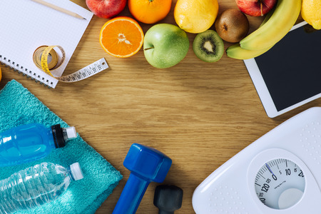 Foto de Fitness and weight loss concept, dumbbells, white scale, towels, fruit, tape measure and digital tablet on a wooden table, top view - Imagen libre de derechos