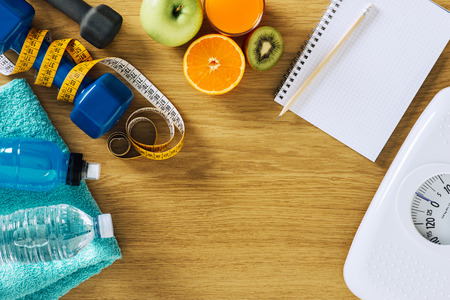 Fitness and weight loss concept, dumbbells, white scale, notebook, tape measure and fruit on a wooden table, top view