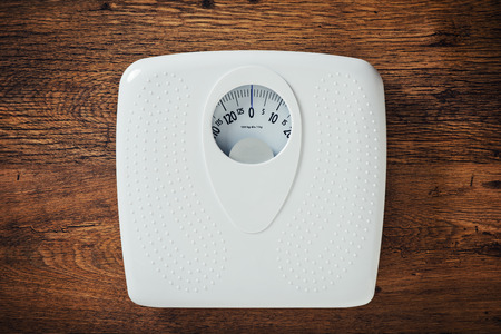 Foto de White scale on a wooden table top view, fitness and weight loss concept - Imagen libre de derechos