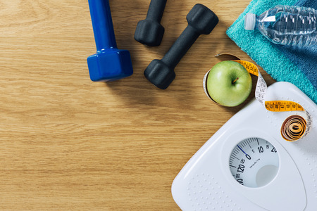 Photo pour Fitness and weight loss concept, dumbbells, tape measure, white scale towels and water bottle on a wooden table, top view - image libre de droit