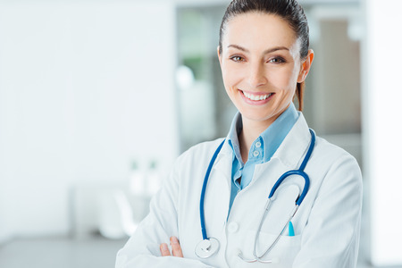 Confident female doctor posing in her office and smiling at camera, health care and prevention concept