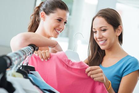 Foto de Pretty smiling girls shopping women's clothing at the store, fashion and retail concept - Imagen libre de derechos