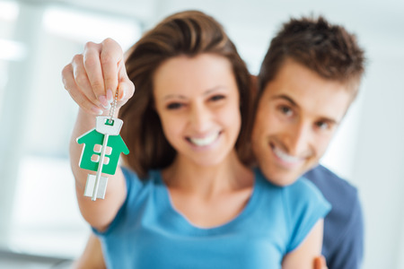 Photo pour Young smiling couple holding their new house keys, real estate and relocation concept - image libre de droit