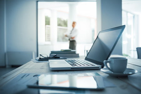 Photo pour Businessman standing with arms crossed in his office, desktop with laptop on foreground, selective focus - image libre de droit